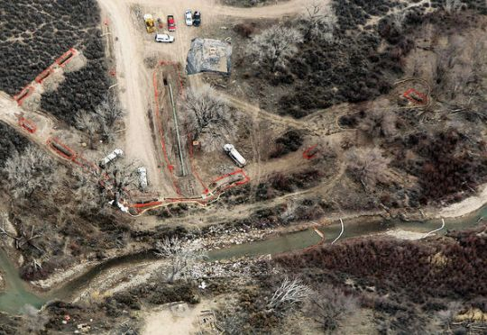 This aerial view was captured in a flyover provided by EcoFlight. It depicts the Parachute Creek leak site looking east shows orange fencing that indicates trenched areas associated with the ongoing investigation, as well as part of the pipeline corridor where 6,000 gallons of liquid hydrocarbons were recovered. Pipelines in the corridor cross under the creek. (Photo by Christopher Tomlinson)