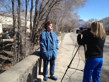 Leslie Robinson (chair, GVCA) talks with KKCO-Ch 11 reporter Christy Dimond at the bridge over Parachute Creek in Parachute, Monday morning.
