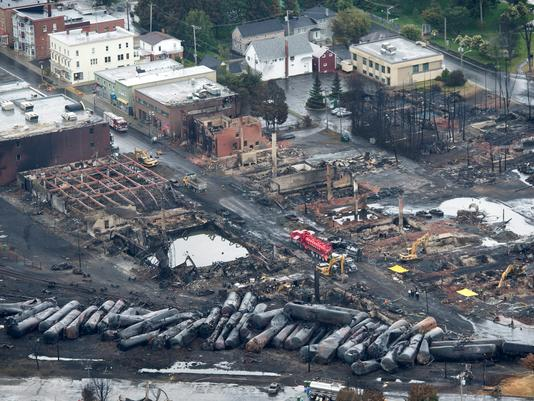 In this aerial photo from July 9, workers comb through the debris after a train derailed causing explosions of railway cars carrying crude oil on in Lac-Megantic, Quebec, Canada. So far, 24 people have died and 50 people are still missing.   [Photo: Paul Chiasson AP]