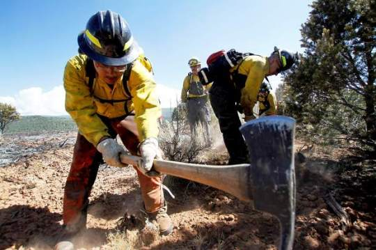 Firefighter Michael Cruz of Grand Valley Fire Department swings his pulaski as he helps construct a fire line on the south side of the Red Canyon Fire on Tuesday. [photo credit: Christopher Mullen - Special to the Post Independent]