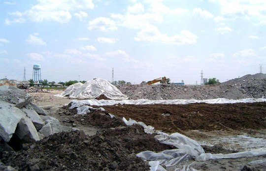 A front end loader is used to spread contaminated soil for aeration and drying -- Bedford Park, IL [Brandenburg]