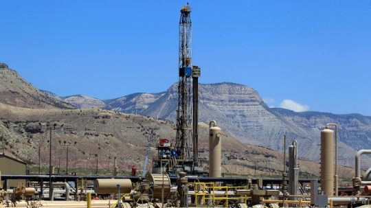 A natural gas drilling rig operates as natural gas piping rises from underground outside Rifle, Colorado [Reuters / George Frey]