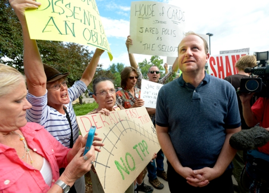 Protestors give Congressman Jared Polis their reaction to the pulling of anti-fracking state ballots initiatives before an appearance by the congressman at the Meadows Branch Library in Boulder on Tuesday evening. Photo by Paul Aiken / The Daily Camera