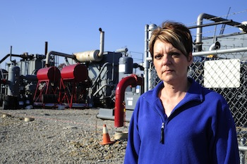 Pam Judy in front of a compressor station. Photo by Mark Schmerling