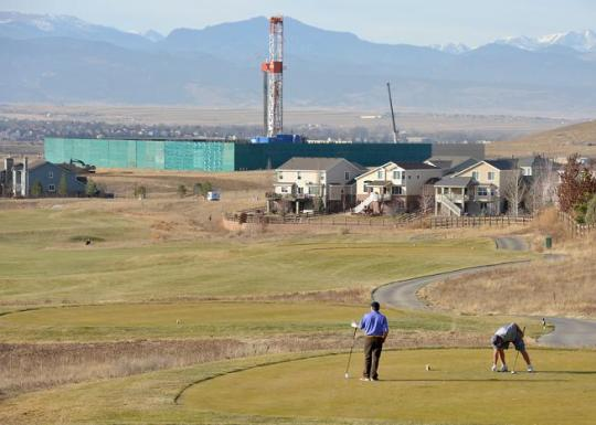 Golfers play a round on the Vista Ridge Golf Club on Friday with the Encana Rig 272 oil/gas drilling rig in the background in Erie. For more photos, go to www.dailycamera.com (David R. Jennings / Daily Camera)