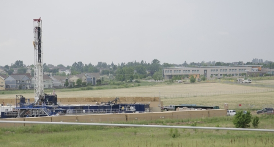 Well pad site near residential subdivision and Red Hawk Elementary School in Erie, CO. Scenes like this won't change after task force fails to address setbacks. [Photo by Aurora Open/SuperStock]