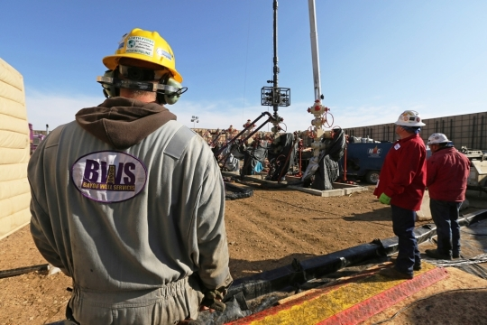 Workers keep an eye on well heads during a hydraulic fracturing operation at an Encana Corp. oil well, near Mead, CO [AP photo]