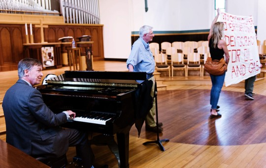 Governor John Hickenlooper plays the piano at First Congregational Church in Boulder on June 8, while about 20 activists shout opposition to his policies regarding oil & gas development. [Photo by Jonathan Castner]